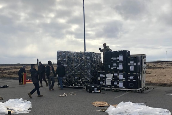 Photo shows large pallets with an assortment of equipment being stack on them for shipment.