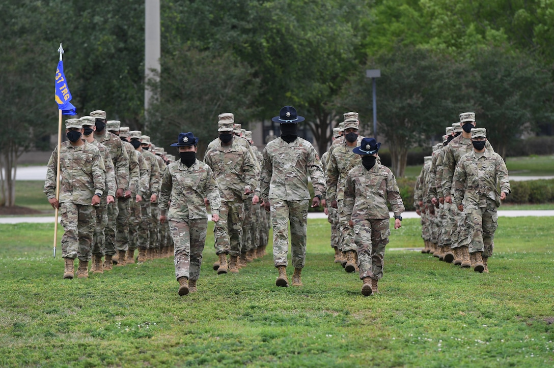 Military training instructors lead graduating Airmen onto the drill pad during the basic military training graduation ceremony at Keesler Air Force Base, Mississippi, May 15, 2020. Nearly 60 Airmen from the 37th Training Wing Detachment 5 completed the six-week basic military training course. Due to safety concerns stemming from COVID-19, the Air Force sent new recruits to Keesler to demonstrate a proof of concept to generate the force at multiple locations during contingencies. The flight was the first to graduate BMT at Keesler since 1968. (U.S. Air Force photo by Kemberly Groue)
