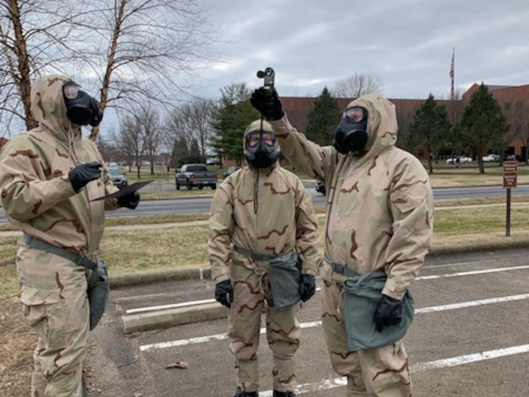 Airmen in protective gear taking weather readings.