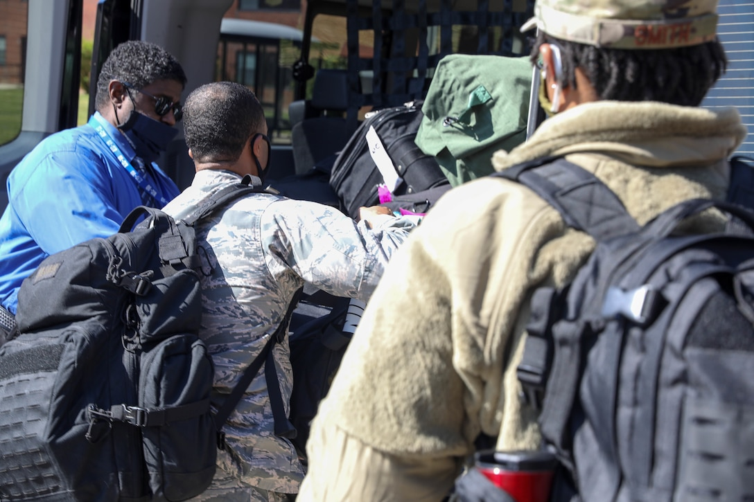 U.S. Air Force Capt. John Nelson (center), psychologist, 59th Medical Group, Randolph Air Force Base, Texas, helps his fellow airmen, including behind Staff Sgt. Le'Aisha Smith (right), mental health technician, 59th Medical Group, Randolph Air Force Base, Texas, by loading up their baggage and personal belongings into the back of the van at Joint Base McGuire-Dix-Lakehurst, NJ, April 28, 2020. Nelson and Smith are a part of a six-member team that will provide behavioral health and support services to the service men and women that are provide care and medical services to COVID-19 patients. U.S. Northern Command, through U.S. Army North, is providing military support to the Federal Emergency Management Agency to help communities in need. (U.S. Army photo by Sgt. Aimee Nordin)