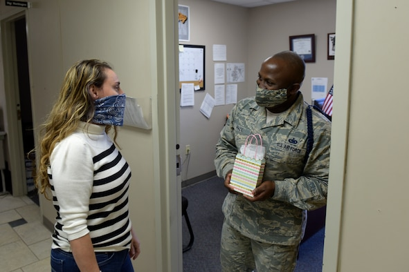 17th Training Wing Violence Prevention Integrator, Donna Casey, presents U.S. Air Force Staff Sgt. Alonso Hall, 316th Training Squadron Military Training Leader, a gift bag in the 316th TRS dormitory on Goodfellow Air Force Base, Texas, May 1, 2020. Gift bags, snacks or thank you cards were given out to MTLs on Goodfellow as part of the Adopt-An-MTL program, thanking them for all that they do. (U.S. Air Force photo by Senior Airman Zachary Chapman)