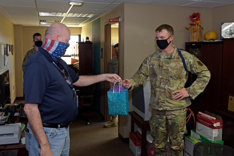 17th Training Wing Community Support Coordinator, David Sullins hands U.S. Air Force Master Sgt. Nicholas Schule, 312th Training Squadron flight chief, a gift bag, as part of the Adopt-An-MTL, in the 312th TRS dormitory on Goodfellow Air Force Base, Texas, May 1, 2020. The Adopt-An-MTL program was created to let the military training leaders know they are not alone and that the Goodfellow family appreciated all they do. (U.S. Air Force photo by Senior Airman Zachary Chapman)