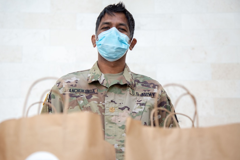 A man in a military uniform and face mask stands ready to distribute food packed in shopping bags.