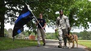 Woman carrying Black flag with blue stripe down middle and man walking with military dog