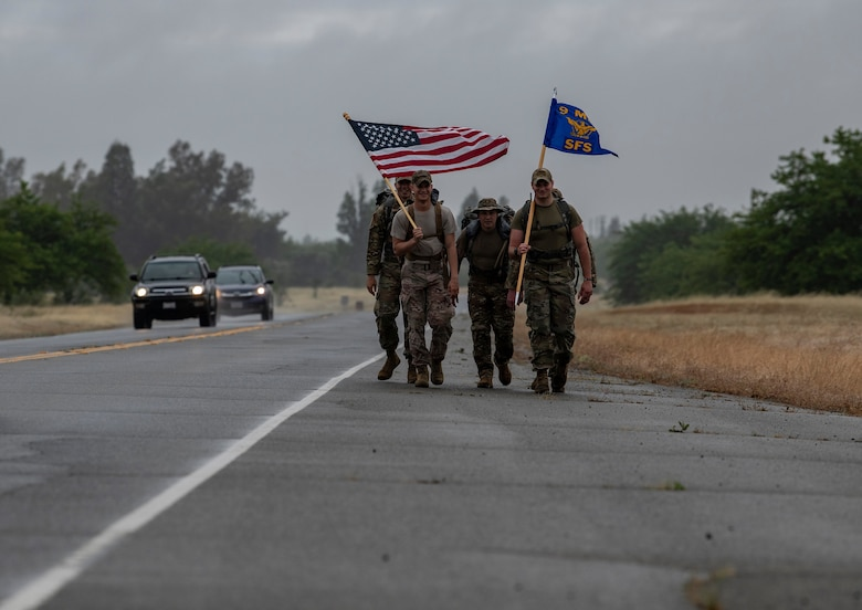 Airmen from the 9th Security Forces Squadron ruck alongside a road as part of Police Week.