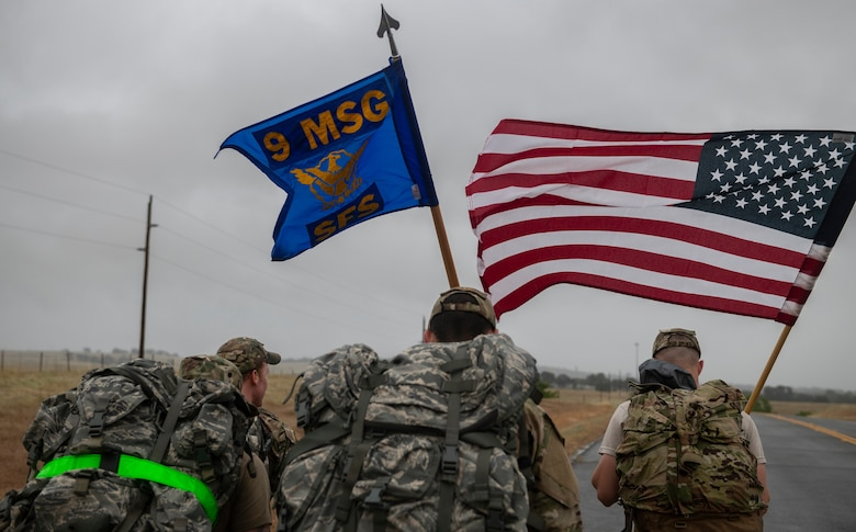 Airmen from the 9th Security Forces Squadron carry a U.S. flag as well as their squadron guidon.