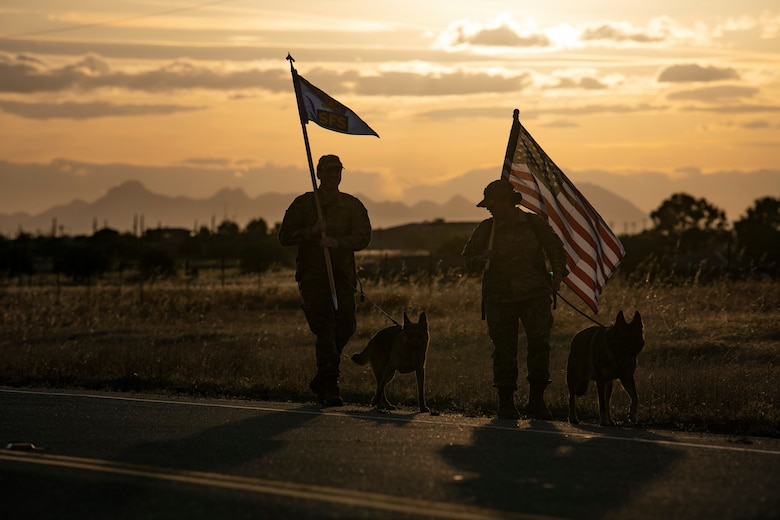 U.S. Air Force Staff Sgt. Sandra Ohfa-Jones, 9th Security Forces Squadron (SFS) trainer, right, and Tech. Sgt. Patrick Harris, 9th SFS commercial vehicle inspection area NCOIC, left, carry the U.S. Flag and 9th SFS guidon as part of Police Week.