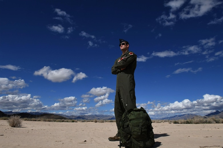 Mq-9 Reaper pilot stands in desert with Ranger ruck sack