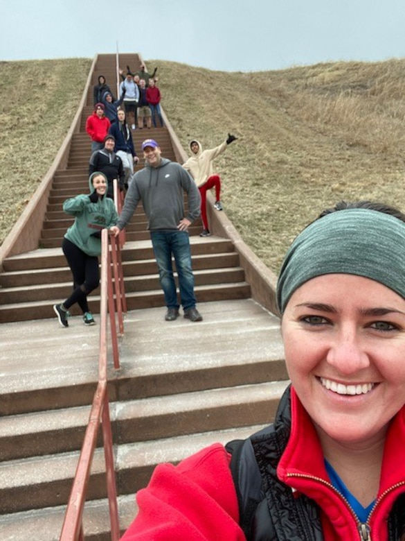 Woman taking selfie with people posing on stairs in background.