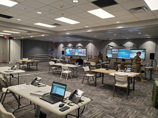 Photo shows large room with tables and laptops being set up.