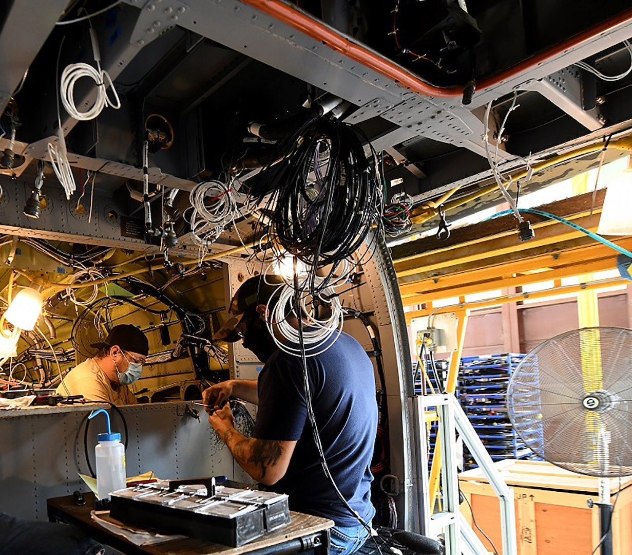 Jonathan Lopez (right) and Michael Lee, aircraft electricians in the assembly repair division at the Corpus Christi Army Depot, Texas, install the data concentrator units wiring as part of the UH-60L to UH-60V helicopter upgrade. (U.S. Army photo by Ervey Martinez)