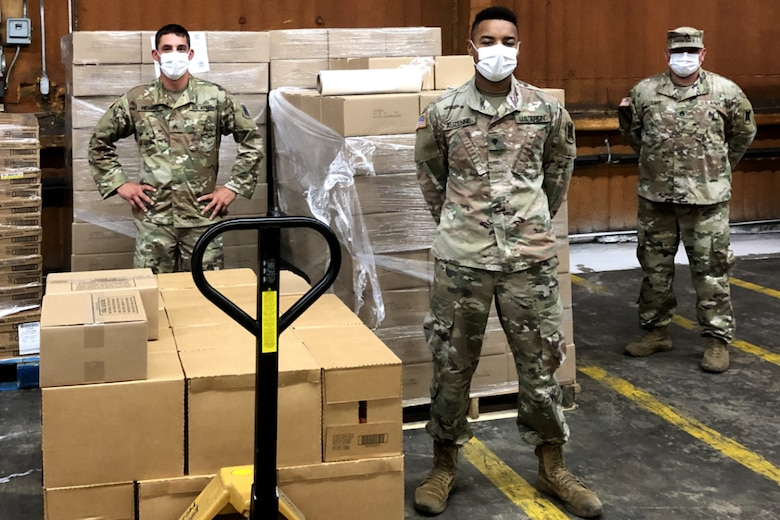 Photo of soldiers standing near pallets of food in a warehouse.