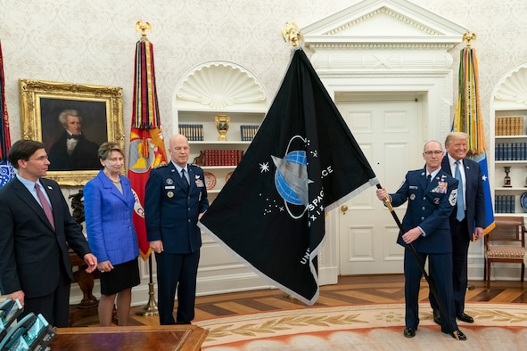 "U.S. Space Command commander Gen. John W. ""Jay"" Raymond and Senior Enlisted Advisor Chief Master Sgt. Roger Towberman present President Donald J. Trump with the Space Force flag in the Oval Office of the White House, May 15, 2020."