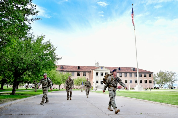75th Security Forces Squadron Defenders walking away from the 75th Air Base Wing Headquarters building. The American flag also appears in the background.