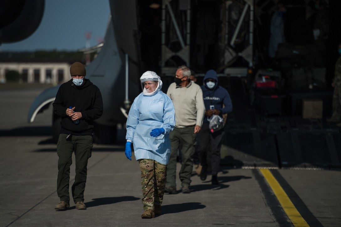 A U.S. Air Force Staff Sgt. Megan Gable, 313th Expeditionary Operations Support Squadron aeromedical evacuation technician, guides COVID-19 patients off a C-17 Globemaster III at Ramstein Air Base, Germany, May 16, 2020.