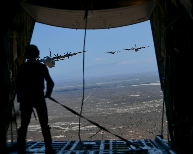 A California Air National Guard loadmaster is seen holding a tie down strap inside the back of a military California Air National Guard C-130J Super Hercules aircraft. In front of him the back of the aircraft's ramp is open to show three additional C-130J Super Hercules aircraft from the California Air National Guard following in close pursuit at a lower altitude above a drop zone in the Palmdale desert.
