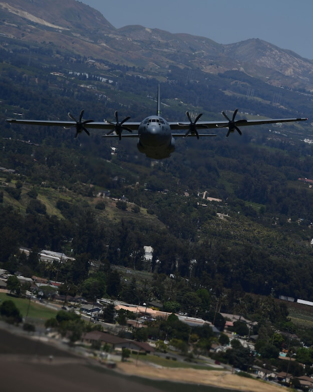 A military California Air National Guard C-130J Super Hercules aircraft is shown flying at a low altitude over the Camarillo Valley.