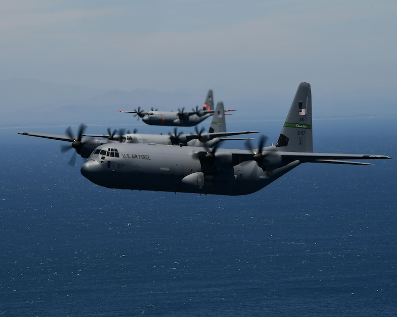 Three military California Air National Guard C-130J aircraft fly in close formation over the blue Pacific Ocean.