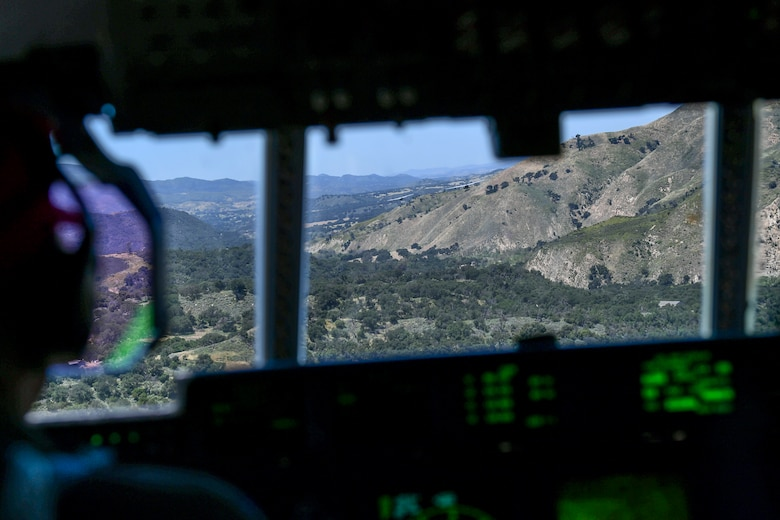 A view from inside the cockpit or flight-deck from the third chair of a military California Air National Guard C-130J Super Hercules aircraft. Inside the cockpit the back of the number one pilot can be seen as he stares into his heads-up-device as he closely follows two additional C-130J Super Hercules Aircraft in a green valley surrounded by a mountainous terrain.