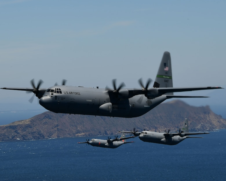 Three military California Air National Guard C-130J aircraft fly in close formation over the blue Pacific Ocean with the Anacapa Islands in the background.