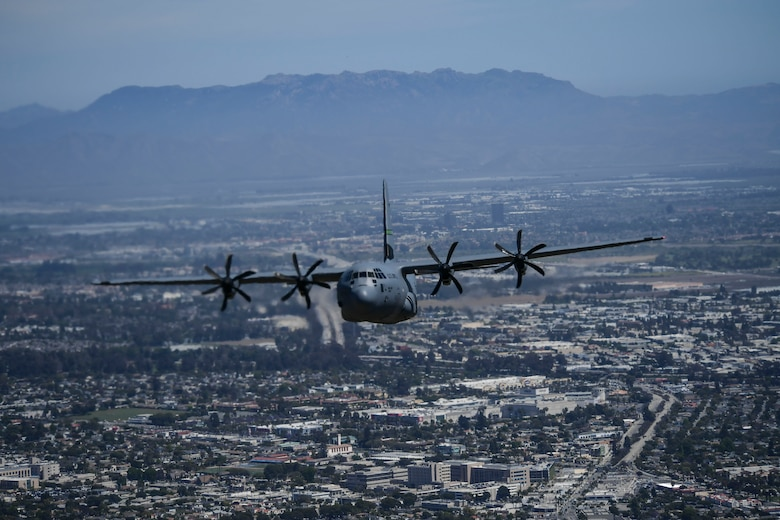 An Image of a Military C-130J Super Hercules aircraft flying over the city of Ventura County.