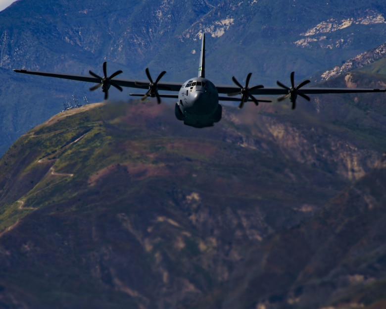 A military C-130J aircraft from the California Air National Guard fly's over green rolling hills above the city of Santa Barbara, California.