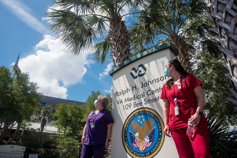 April Cheesebourough and Christina Schenk, VA employees and Air Force spouses, await a flyover saluting healthcare workers in the fight against COVID-19, May 15, 2020, at Ralph H. Johnson VA Medical Center in Charleston, South Carolina. Joint Base Charleston Airmen from the 315th Airlift Wing and 437th Airlift Wing, came together to train during this salute to healthcare workers that flew over several Charleston medical centers.