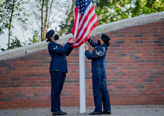 Airmen from the 48th Security Forces Squadron and the 100th SFS raise the U.S. flag during a morning reveille ceremony at Royal Air Force Lakenheath, England, May 11, 2020. The ceremony was held to mark the beginning of National Police Week, an annual time of remembrance to commemorate those law enforcement officers who have lost their lives in the line of duty. (U.S. Air Force photo by Airman 1st Class Jessi Monte)