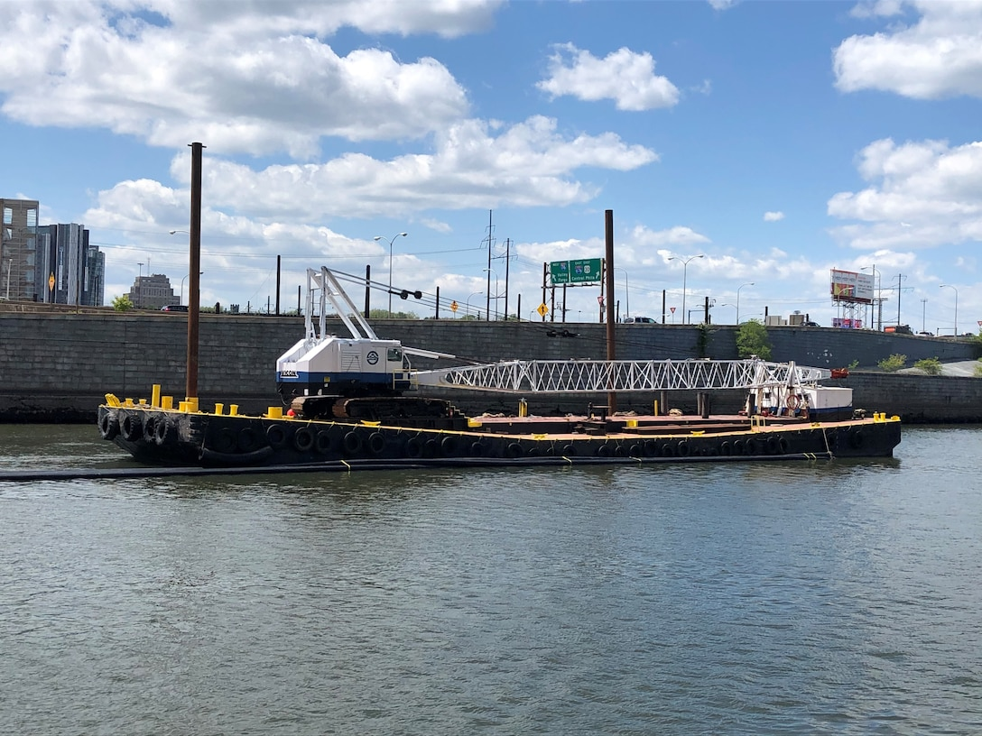 A crane barge, owned and operated by Atlantic Subsea Inc. is positioned south of the Route 676 Bridge in Philadelphia.   The U.S. Army Corps of Engineers Philadelphia District is managing a project to dredge portions of the Schuylkill River above the Fairmount Dam in Philadelphia, PA. The project is funded by the City of Philadelphia and by private donations. Atlantic Subsea Inc. is the contractor.