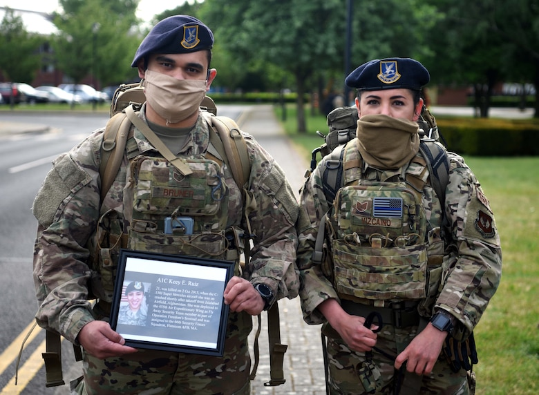 Staff Sgt. Anthony Bruner, 100th Security Forces Squadron member, and Tech. Sgt. Jessica Vizcaino, 100th SFS flight chief, pose with a photo of Airman 1st Class Kcey Ruiz during the 100th SFS Memorial Ruck March at RAF Mildenhall, England, May 13, 2020. Ruiz, a former security forces Airman, died in 2015 while deployed to Afghanistan in support of Operation Freedom's Sentinel. (U.S. Air Force photo by Senior Airman Brandon Esau)