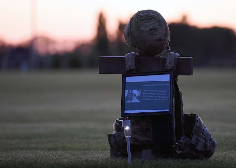 """A memorial display for Airman 1st Class Jason D. Nathan rests during a candlelight vigil to honor the """"Fallen 14"""" during events to commemorate National Police Week at RAF Mildenhall, England, May 14, 2020. Nathan, a former 48th Security Forces Squadron Airman, died in Iraq in 2007 from wounds suffered from an IED that detonated near his vehicle. (US. Air Force photo by Senior Airman Brandon Esau)"""