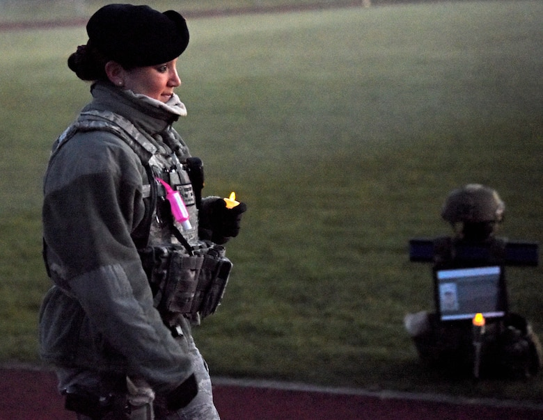 """Master Sgt. Rebecca Swift, 100th Security Forces Squadron flight chief, walks during a candlelight vigil to honor the """"Fallen 14"""" during events to commemorate National Police Week at RAF Mildenhall, England, May 14, 2020. The Fallen 14 represents the number of SF Airmen who've lost their lives in the line of duty since 9/11. (U.S. Air Force photo by Senior Airman Brandon Esau)"""