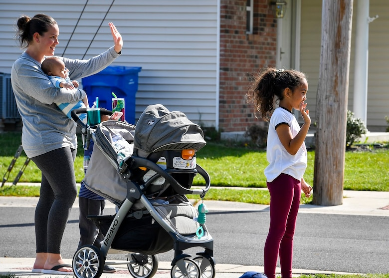 A family waves to Security Forces and Police personnel as they drive by during a National Police Week parade at Joint Base McGuire-Dix-Lakehurst, N.J., May 13, 2020. With the on-going COVID-19 pandemic, the parade was held for families to get out and have fun while maintaining social distancing. NPW runs from May 10-16 with the installation conducting a parade, 24-hour ruck march and a vigil that will honor defenders past and present. (U.S. Air Force photo by Staff Sgt. Jake Carter)