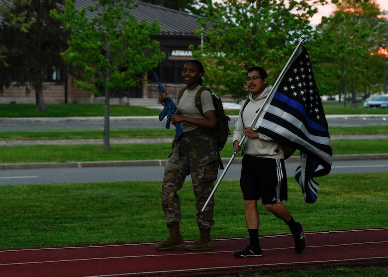 Senior Airman Grace Wright and Senior Airman Jovane Concha, 87th Security Forces Squadron members, ruck march around the McGuire Fitness Center track on Joint Base McGuire-Dix-Lakehurst, N.J., May 14, 2020. The ruck began at 9 a.m., with teams of two carrying a flag and training weapon for one hour blocks for 24-consecutive hours. National Police Week runs from May 10-16 with the 87th SFS conducting a parade, 24-hour ruck march and a vigil that will honor defenders past and present. (U.S. Air Force photo by Staff Sgt. Jake Carter)