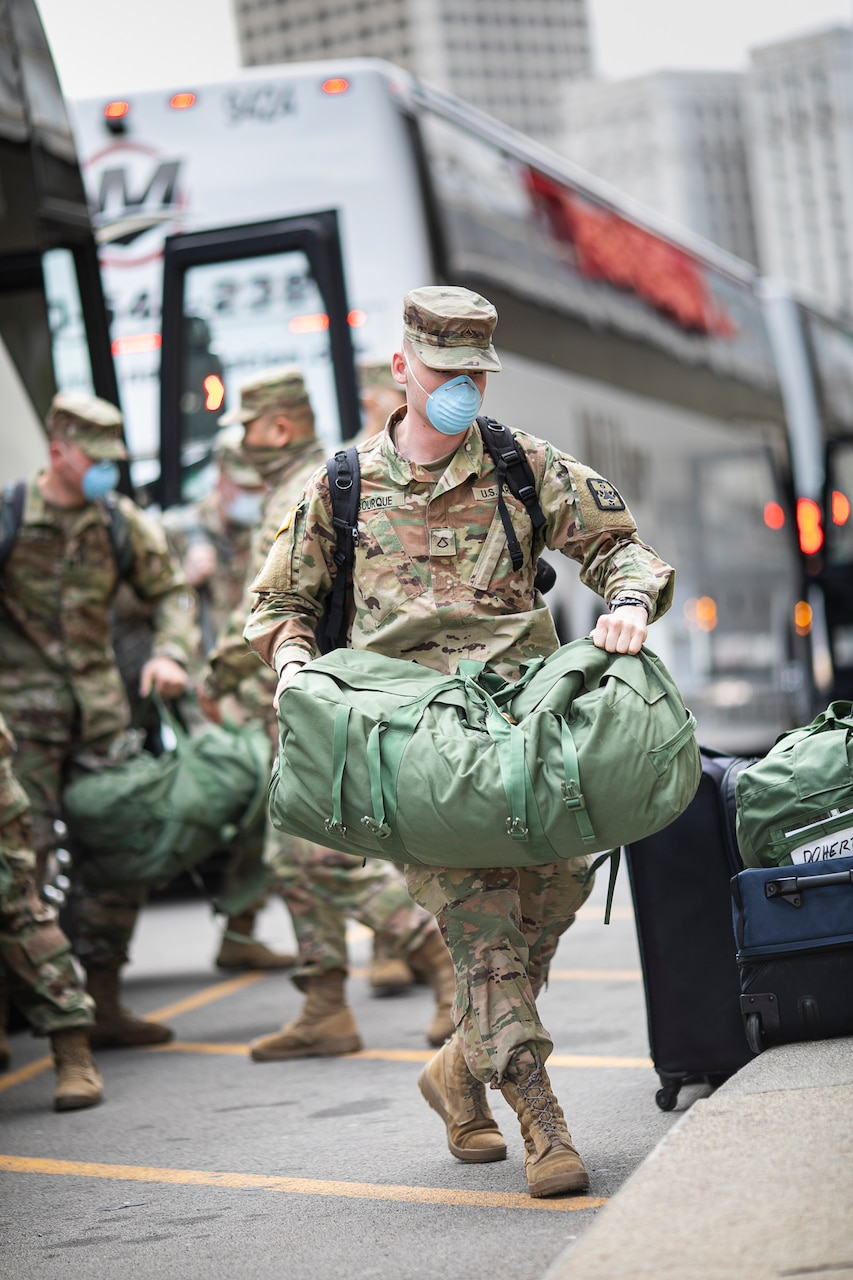 Soldiers in uniform and face masks carry duffle bags off a bus.