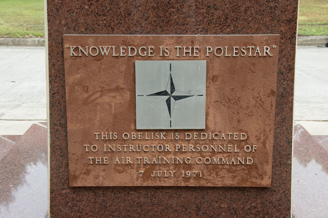 """A close-up picture of the dedication plaque that reads """"knowledge is the pole star"""" and """"this obelisk is dedicated to instructor personnel of the Air Training Command, 7 July 1971."""""""
