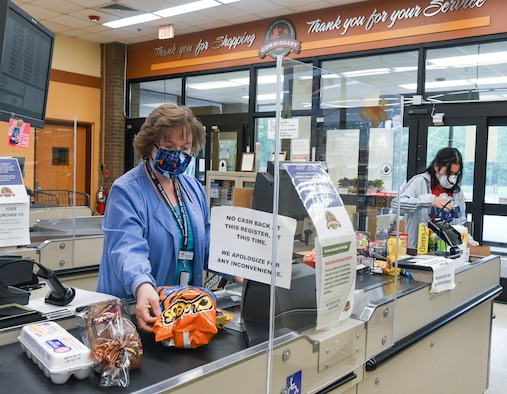 Store teller Tina Lawson scans a customer's purchases, as bagger Sarah Goldston bags the items, May 5, 2020, at the Arnold Air Force Base Commissary, while taking measures to reduce the risk of coronavirus transmission. The Arnold Air Force Base Commissary and Base Exchange have remained open to serve their customers throughout the coronavirus crisis. (U.S. Air Force photo by Jill Pickett) (This image was altered by obscuring a badge for security purposes.)
