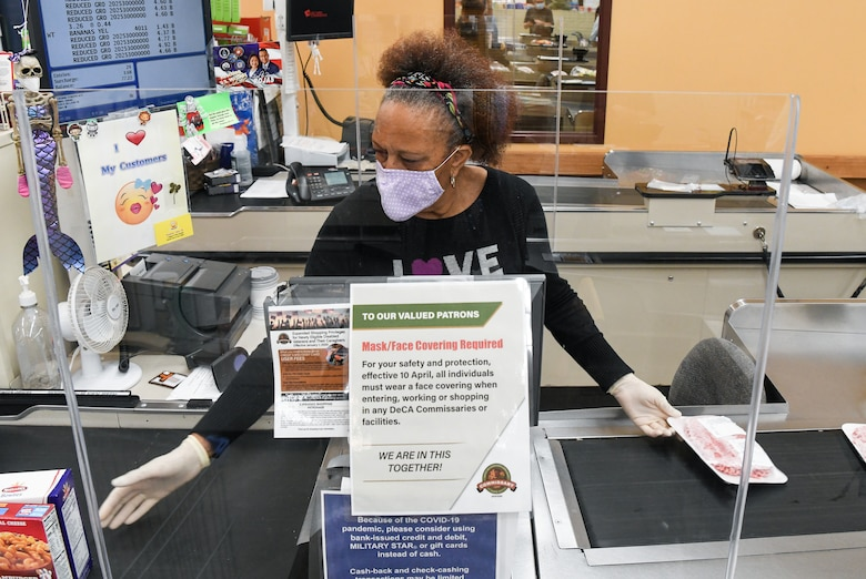 Store teller Wynetta Johnson scans a customer's purchases May 5, 2020, at the Arnold Air Force Base Commissary, while taking measures to reduce the risk of coronavirus transmission. The Arnold Air Force Base Commissary and Base Exchange have remained open to serve their customers throughout the coronavirus crisis. (U.S. Air Force photo by Jill Pickett)