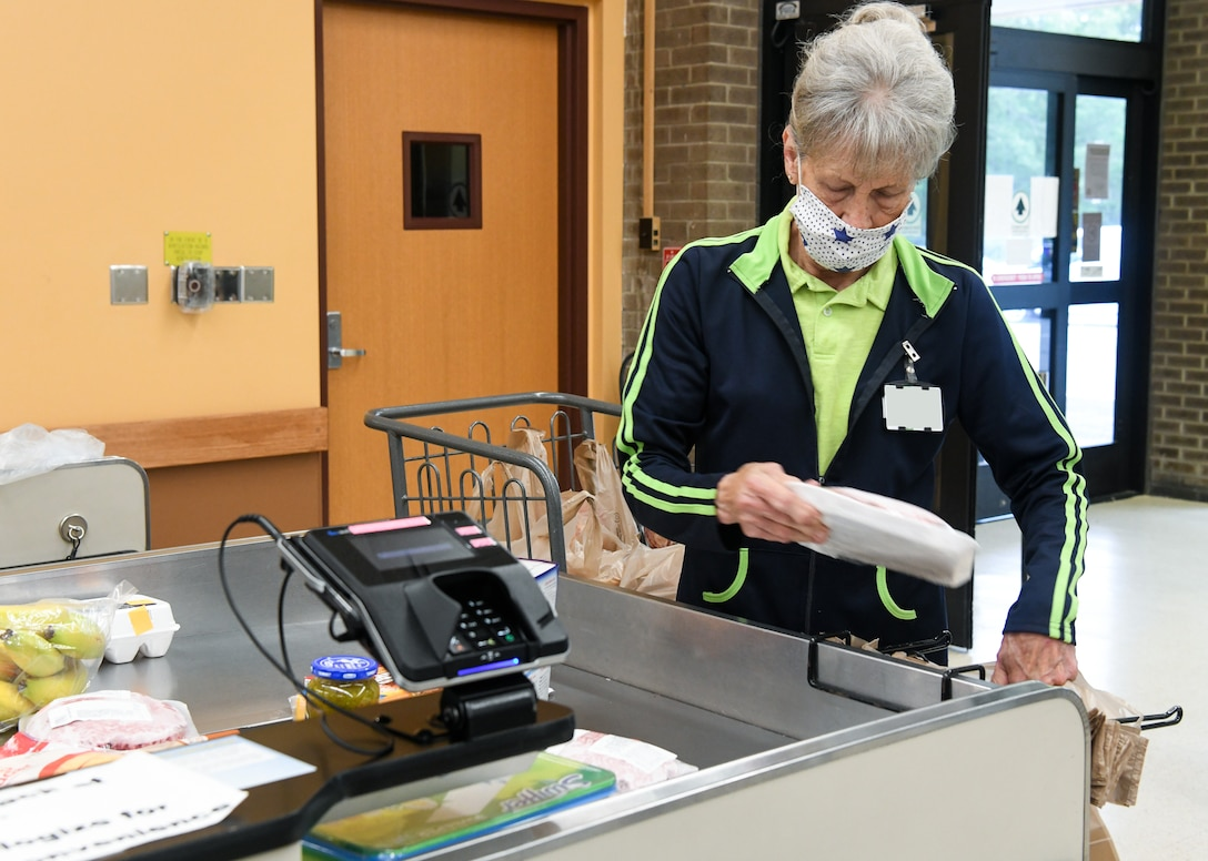 Bagger Mary Cathey bags a customer's purchases, May 5, 2020, at the Arnold Air Force Base Commissary, while taking measures to reduce the risk of coronavirus transmission. The Arnold Air Force Base Commissary and Base Exchange have remained open to serve their customers throughout the coronavirus crisis. (U.S. Air Force photo by Jill Pickett) (This image was altered by obscuring a badge for security purposes.)