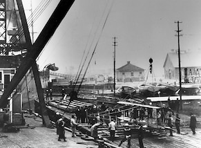 In this file photo provided by the U.S. Naval Historical Center taken in November 1910, a floating crane from Norfolk Naval Shipyard lifts a Curtiss Model D biplane to the deck of the Chester-class cruiser USS Birmingham (CL 2). Civilian aviator Eugene B. Ely flew the plane off Birmingham on Nov. 14, 1910, the first aircraft launch from a warship.