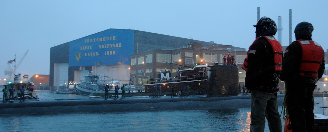 Line handlers stand at the ready to moor the Los Angeles-class attack submarine USS Miami (SSN 755) as the boat arrives at Portsmouth Naval Shipyard to begin an engineered overhaul period.