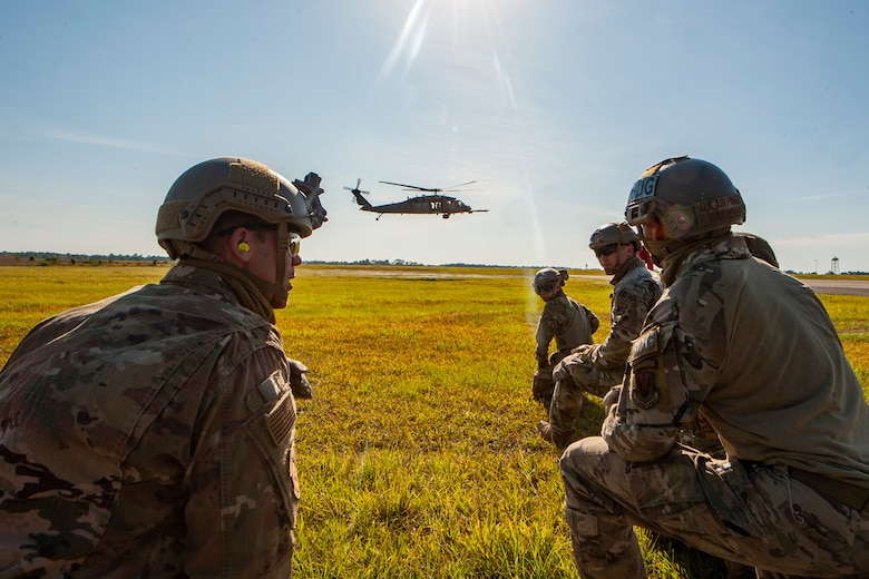 A photo of airmen talking while a helicopter flies in the background.