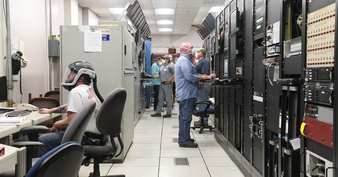 Seven Hroncich, left, an instrument technician, Robert Bradford, center right, an electrician, Kevin Thompson, right, test operations engineer, Tim Mullins, an outside machinist, and others prepare for a test run in the Arnold Engineering Development Complex (AEDC) Arcs Test Facility Control Room, May 5, 2020, at Arnold Air Force Base, Tenn. The Arcs Facility provides aerothermal ground test simulations of hypersonic flight over a wide range of velocities and pressure altitudes in support of materials and structures development. Team members are maintaining social distancing when possible and wearing masks when not so they can continue the critical national defense mission of AEDC. (U.S. Air Force photo by Jill Pickett) (This image was altered by obscuring items for security purposes.)