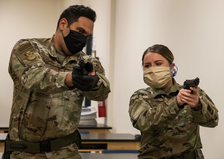 Staff Sgt. Jose Bracero-Camareno, 436th Security Forces Squadron combat arms instructor, teaches Airman 1st Class Kaleigh O'Hara, 436th Comptroller Squadron budget analyst, proper M9 sight alignment May 13, 2020, at Dover Air Force Base, Delaware. Bracero-Camareno instructed O'Hara and other Team Dover members on the M9 prior to their upcoming deployment or permanent change of station. (U.S. Air Force photo by Roland Balik)