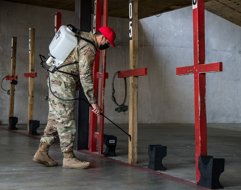 Staff Sgt. Jose Bracero-Camareno, 436th Security Forces Squadron combat arms instructor, sanitizes shooting stations after an M9 Combat Arms Training and Maintenance qualification course May 13, 2020, at Dover Air Force Base, Delaware. Bracero-Camareno and other CATM instructors provided Team Dover members M4 and M9 training prior to their upcoming deployment or permanent change of station. A shelter-in-place order was issued in mid-March to help mitigate the spread of COVID-19. (U.S. Air Force photo by Roland Balik)