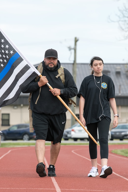 "Detective Rafael Gonzalez, 436th Security Forces Squadron, walks with his daughter, Olivia, during the 2020 Police Week Ruck March May 14, 2020, at Dover Air Force Base, Delaware. Gonzalez is carrying a 35-pound ruck on his back and a ""Thin Blue Line"" version of the American flag, which represents support for law enforcement. (U.S. Air Force photo by Mauricio Campino)"