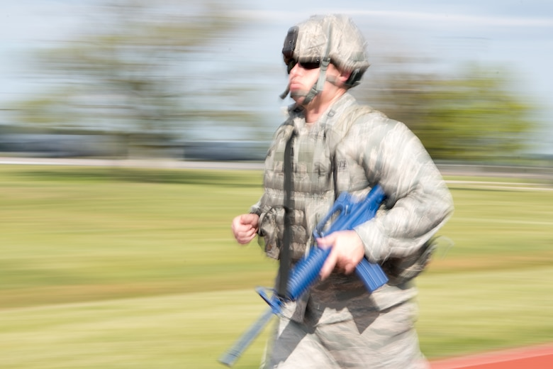 Capt. James Scott, 436th Security Forces Squadron operations officer, runs in full body armor with a training rifle during the 2020 Police Week Ruck March May 14, 2020, at Dover Air Force Base, Delaware. Participants signed up to walk or run for a 30-minute time slot, but some participants went far beyond that, traveling distances of up to 20 miles. (U.S. Air Force photo by Mauricio Campino)