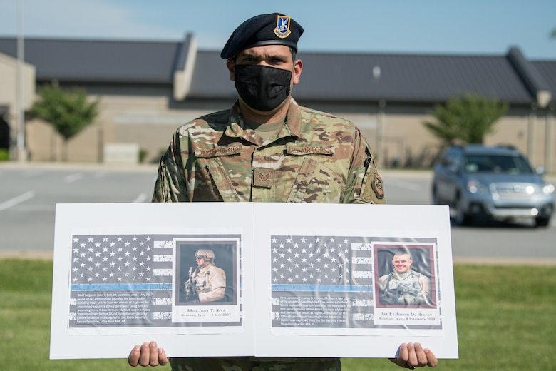 Staff Sgt. Jose Bracero-Camareno, 436th Security Forces Squadron combat arms instructor, holds photos of two fallen defenders during a retreat ceremony on Peace Officers Memorial Day May 15, 2020, at Dover Air Force Base, Delaware. The ceremony commemorating fallen military and civilian law enforcement officers marked the end of National Police Week 2020. (U.S. Air Force photo by Mauricio Campino)