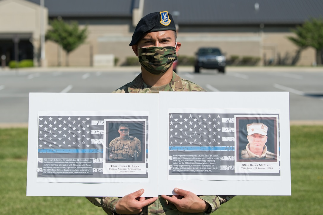 Senior Airman Vincent Leal, 436th Security Forces Squadron Raven team leader, holds photos of two fallen defenders during a retreat ceremony on Peace Officers Memorial Day May 15, 2020, at Dover Air Force Base, Delaware. The ceremony commemorating fallen military and civilian law enforcement officers marked the end of National Police Week 2020. (U.S. Air Force photo by Mauricio Campino)
