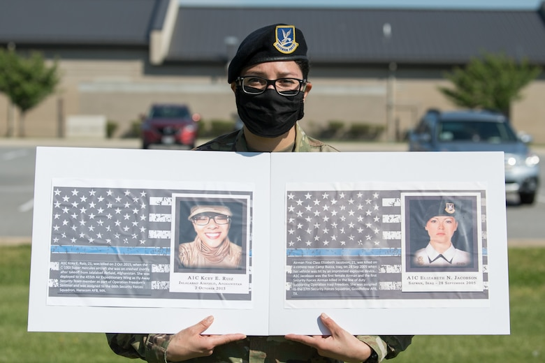 Senior Airman Theresa Braack, 436th Security Forces Squadron military working dog handler, holds photos of two fallen defenders during a retreat ceremony on Peace Officers Memorial Day May 15, 2020, at Dover Air Force Base, Delaware. The ceremony commemorating fallen military and civilian law enforcement officers marked the end of National Police Week 2020. (U.S. Air Force photo by Mauricio Campino)